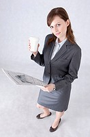 Businesswoman holding a cup and newspaper and looking up