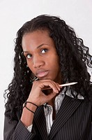 Close_up of businesswoman holding a pencil and looking up