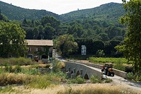 Small tractor crossing bridge, wine chateau in the Corbieres region, Department Aude, France