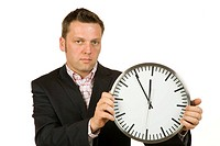 40 year-old businessman holding a clock showing the time of 5-to-12