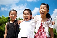 Three children standing in a row with arms around and shouting happily