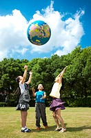 Three children standing on the lawn and playing with globe together