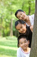 Three children hiding behind a tree and looking at the camera with smile