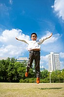 Little boy jumping in mid-air with arms outstretched and looking down (thumbnail)
