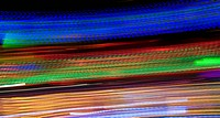 An energetic abstract of the lights of a spinning fairground ride at night showing the linear light motion trails effect created by panning during a l...