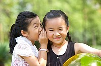 Two girls whispering and smiling happily, Child