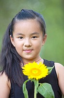 Close_up of girl holding a sunflower and smiling at the camera