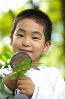 Close_up of boy holding magnifying glass and smiling at the camera