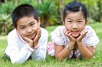 Two children lying on the lawn with head in hands and looking at the camera, Child