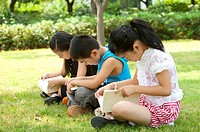 Three children sitting in a row and reading book together, Child
