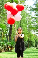 Girl standing on the lawn and holding balloons with smile