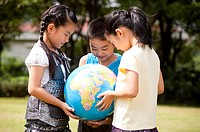 Three children holding the globe together and looking down