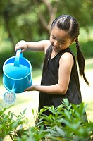 Girl holding watering can and watering
