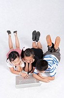 Child, Children lying on front and using laptop together