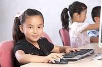 Child, Children using computer and looking at the camera with smile
