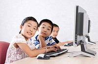 Child, Children using computer and looking at the camera together