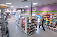 Female customer walking past shelves in a drugstore, pharmacy, Ihr Platz in Berlin_Neukoelln, Germany