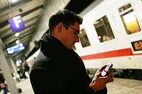 DEU Germany Man with a mobile phone on the platform of a railway station. ,