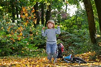 little boy throwing autmn foliage away