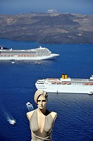 Mannequin doll from tourist shop, cruise ships and Nea Kameni island, viewed from Fira town, Santorini island, Greece