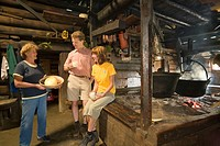Couple sitting at open fireplace and drinking fresh milk, Anna Gruber showing them fresh handmade butter, Karseggalm 1603 m, one of the oldest mountai...