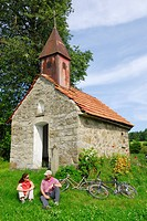 Cyclists resting near a chapel, Bad Koetzting, Bavarian Forest, Upper Palatinate, Bavaria, Germany