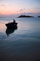 fishing boat in front of tropical island at twilight, Maldives, Indian Ocean
