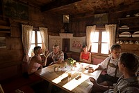 Group of people sitting in the Karseggalm Hut 1603 m, one of the oldest mountain hut in the valley, Grossarl Valley, Salzburg, Austria
