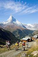 Group of hikers arriving the mountain village Findeln, Matterhorn 4478 m in background, Zermatt, Valais, Switzerland