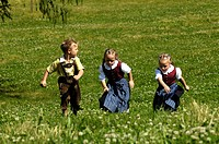 Girl and boy wearing traditional clothes running through an Alpine meadow, Farm holidays, Agriculture, South Tyrol, Italy
