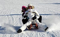 Two women on a sledge, sledging down a slope, Fun in the snow, South Tyrol, Italy