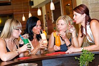 four young women sitting at the bar drinking cocktails together