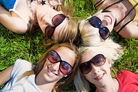 four teenage girls with sunglasses lying in a meadow with a smile and the heads together, symbolic for ´circle of friends´