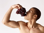 Barechested man eating grapes
