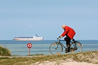 Cyclist and cargo ship on the North sea, Knokke, Belgium