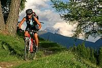 Female mountain biker on the Karer pass with Pala group in the background, Dolomites, Italy