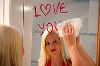 young blond woman wiping off a love message on the mirror