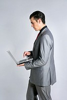 Businessman in gray suit holding laptop computer at studio
