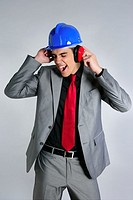 Businessman with blue hardhat and safety headphones for noise