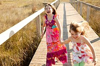Teen two girls running outdoor at the park, hippy pink dress