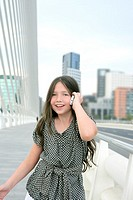 Adorable teenager little girl talking phone downtown in city bridge