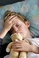 Boy with a fever holding his forehead, which feels hot to the touch due to a high body temperature. He is lying in bed to recover, with cuddly toys to...