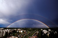 Double rainbow over a town amid trees.