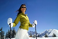young female skier with sunglasses, enjoying the winter holidays in the mountains, Austria, Alps