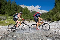 man and woman with mountain bikes on a tour in the alpine landscape, crossing a mountain creek, Austria, Upper Austria, Gmunden