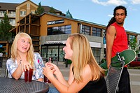 dark_skinned skateboarder looking at two young blond women, sitting at a table, drinking lemonade