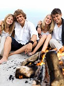 two young couples sitting at a campfire on the beach