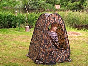 child sitting in camouflage tent watching birds, Germany