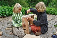children are making an apple dehydrator, child is nailing side parts together, Germany