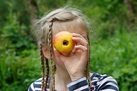 girl is looking through an apple from which the core was removed, Germany